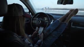 女孩坐轻松在汽车 她写SMS 窗口外是一座美丽的风景、河和桥梁 4K减慢 影视素材
