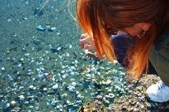 女孩弯曲在海滩收集在沙子的壳 免版税库存图片