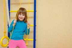 女孩快乐地坐体育梯子 免版税库存照片