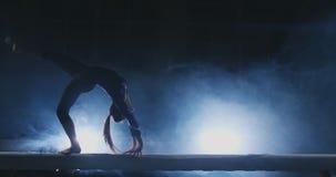 女孩在体育体操衣物进行在注册背后照明的一个把戏和慢动作 烟和蓝色 跳跃和 股票视频