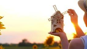 女孩在她的手上拿着在一块麦田的一个玩具磨房在日落的背景 股票录像