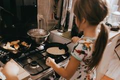 女孩在小的舒适厨房里帮助她的烹调薄煎饼早餐的母亲 库存图片