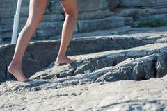 女孩在岩石赤足去,爬上 免版税库存照片