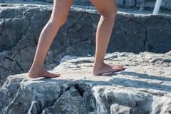 女孩在岩石赤足去,爬上 库存图片
