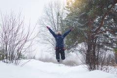 女孩在冬天,跳在冬天森林里的女孩高兴 免版税库存照片