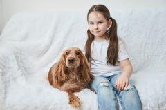 女孩在有红色狗的白色沙发使用 免版税库存照片