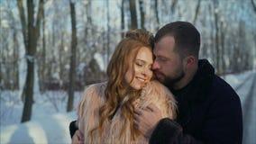 女孩和男孩在冬天取暖在公园 人和女孩在冬天森林年轻夫妇走休息 股票视频