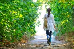 女孩沿道路走在森林到光 免版税图库摄影
