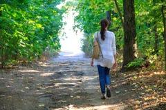 女孩沿道路走在森林到光 库存照片