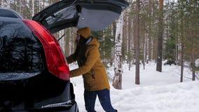 女孩游人在汽车的后车箱投入他的背包 股票视频