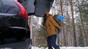 女孩游人在汽车的后车箱投入他的背包 影视素材