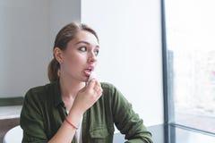 女孩抹她的嘴唇与餐巾吃完在餐馆 抹她的嘴吃完女孩的画象 免版税库存照片