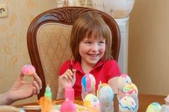 女孩是复活节的乐趣绘的鸡蛋 免版税库存图片