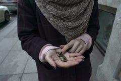 女孩拿着在她的棕榈的一块零钱 图库摄影