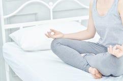 女孩穿灰色衬衣和裤子,坐在床垫的瑜伽 库存图片