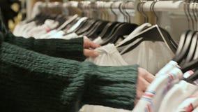 女孩的手的特写镜头在选择衣裳的商店垂悬在挂衣架待售 股票录像
