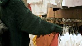 女孩的手的特写镜头在选择衣裳的商店垂悬在挂衣架待售 影视素材
