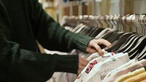 女孩的手的特写镜头在选择衣裳的商店垂悬在挂衣架待售 股票视频