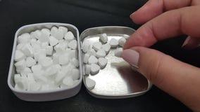 女孩采取从开放金属箱子盖子的一个小白色糖果  图库摄影