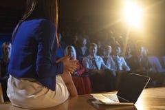 女实业家坐与膝上型计算机和谈论与观众 库存照片