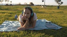 女性在草在公园和听放置到在耳机的音乐 库存照片