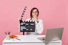 女性医生在书写工作在有医疗文件举行板的计算机在被隔绝的医院坐粉红彩笔墙壁 库存照片