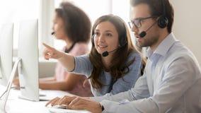 女性指向计算机的电话中心代理帮助的男性同事 免版税库存图片