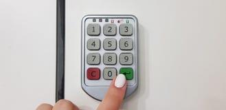 女性手指推挤绿色在安全白色衣物柜的门的输入键 免版税库存图片