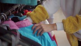 女性手接触与嬉戏温暖的夹克的挂衣架在服装店 股票视频
