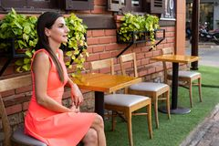 女性等待某人在会议的街道上的一个咖啡馆的,摇她的手对朋友,4k 免版税库存图片