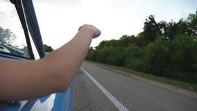 女性胳膊在使用与风的减速火箭的汽车外面在夏天旅行期间 挥动用她的在风的手的少妇在旅行 股票视频