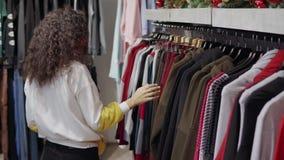 女性顾客在服装店在机架购物,微笑着并且看 股票录像