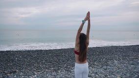 女运动员在小卵石在早晨时间的海海滩舒展,单独站立 影视素材