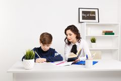 女老师帮助青少年的男孩做他的家庭作业 一起执行家庭作业 库存照片