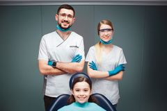 好正面男性和女性牙医有女孩的牙齿椅子的 他们看起来平直和微笑 成人握手横渡 库存图片