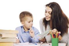 妈妈帮助她的儿子做家庭作业,隔绝在白色背景 柔软,爱 免版税图库摄影
