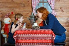 妈妈和女儿从俄国式茶炊和谈话的饮料茶 库存照片