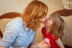 妈妈和女儿食用复活节的乐趣绘的鸡蛋 库存照片
