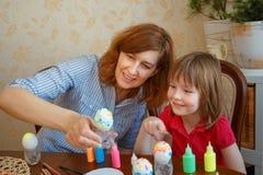 妈妈和女儿食用复活节的乐趣绘的鸡蛋 免版税库存图片