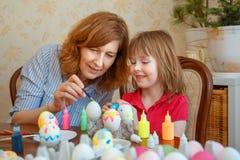 妈妈和女儿食用复活节的乐趣绘的鸡蛋 库存图片
