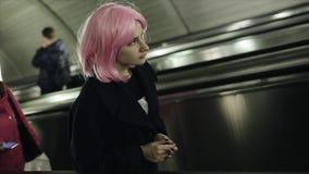 妇女侧视图有桃红色头发的使用在地铁的自动扶梯 影视素材