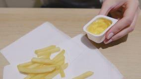 妇女吃薯条用在咖啡馆的乳酪调味料 特写镜头手 股票录像