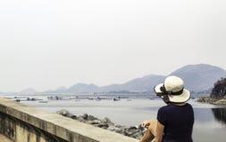 妇女坐混凝土板背景木筏浮动养鱼在水和山在Krasiew水坝,Supanburi 免版税库存图片