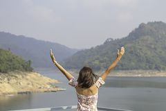 妇女培养他们的胳膊背景山和水在Khun丹Prakan Chon水坝,Nakhon Nayok在泰国 免版税库存图片