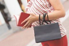 妇女在她的手和小笔记本上站立与一个黑纸袋 背景袋子概念行程购物的白人妇女 生存珊瑚 文本的空间在袋子 免版税库存照片