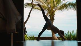 妇女剪影在巴厘岛实践在山位置的瑜伽,舒展腿,在海滩,美丽的景色,自然声音 股票录像
