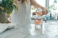妇女倾吐的kombucha在厨房里 免版税图库摄影