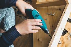 妇女汇编木家具,修理或修理有钻子工具的房子 现代生存概念 免版税库存图片