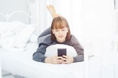 妇女是休息和演奏手机 图库摄影