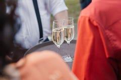 妇女拿着两杯在盘子的香槟 库存照片